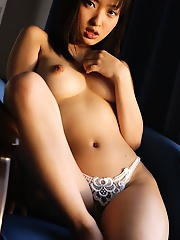 Asian model is nude and showing off her big tits and tight ass while playing
